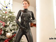 Kinky redhead in a parsimonious black latex costume rubs her wet pussy on the floor while moaning